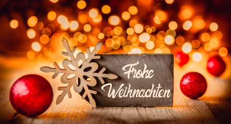 Plate With German Calligraphy Frohe Weihnachten Means Merry Christmas. Sparkling and Glittering Lights Background. Christmas Decoration Like Red Balls And Snowflake