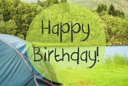 English Text Happy Birthday. Camping Holiday In Norway At Lake Or River. Green Grass And Forest In Background. Tent In The Front