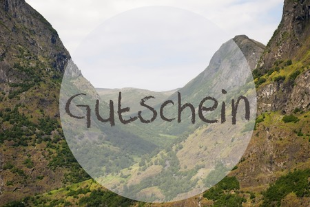 German Text Gutschein Means Voucher. Valley With Mountains In Norway. Peaceful Landscape, Scenery With Grass, Trees And Rocks. Banco de Imagens