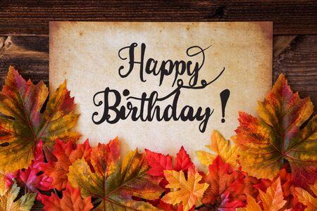 Vieux papier avec texte joyeux anniversaire, décoration de feuilles colorées Banque d'images