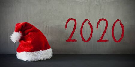 Red Santa Hat, Text 2020, Grey Crunchy Background Imagens - 130686766