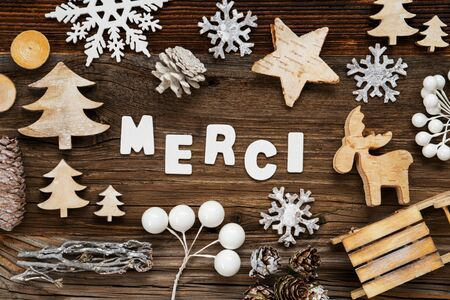 White Letters Building The Word Merci Means Thank You. Wooden Christmas Decoration Like Tree, Sled And Star. Brown Wooden Background