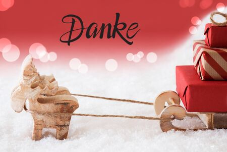 Reindeer With Sled And Christmas Gifts And Snow. Red Sparkling Background With German Calligraphy Danke Means Thank You