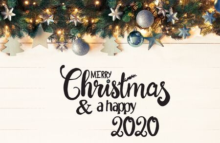 English Calligraphy Merry Christmas And A Happy 2020. Retro Christmas Banner With Turquoise Christmas Decoration And Fir Branches With Fairy Lights