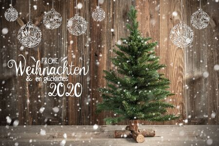 German Calligraphy Frohe Weihnachten Und Ein Glueckliches 2020 Means Merry Christmas And Happy New Year 2020. Christmas Tree Infront Of Brown Wooden Background With Snow And Decoration Reklamní fotografie