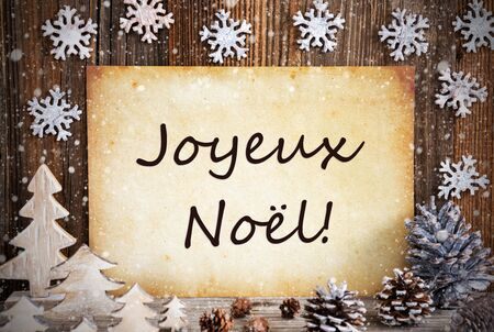 Old Paper With French Text Joyeux Noel Means Merry Christmas. Christmas Decoration Like Tree, Fir Cone And Snow. Brown Wooden Background