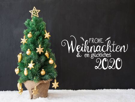 German Calligraphy Frohe Weihnachten Und Ein Glueckliches 2020 Means Merry Christmas And A Happy 2020. Christmas Tree With Golden Ball Ornament And Snow. Black Wooden Background