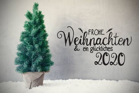 German Calligraphy Frohe Weihnachten Und Ein Glueckliches 2020 Means Merry Christmas And A Happy 2020. Chrismas Tree On Snow. Gray Cement Background Stock Photo