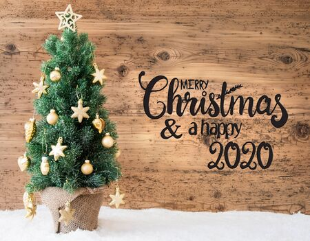 English Calligraphy Merry Christmas And A Happy 2020. Christmas Tree With Golden Ball Ornament And Snow. Brown Wooden Background Reklamní fotografie