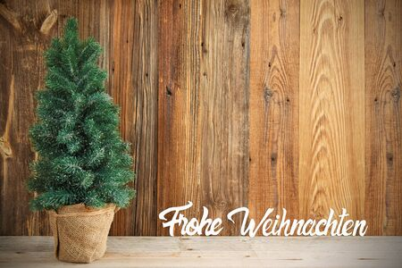 Christmas Tree With Wooden Background. German Calligraphy Frohe Weihnachten Means Merry Christmas