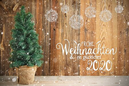 Christmas Tree With Wooden Background, Snow And Christmas Ornament. German Calligraphy Frohe Weihnachten Und Ein Glueckliches 2020 Means Merry Christmas And Happy 2020