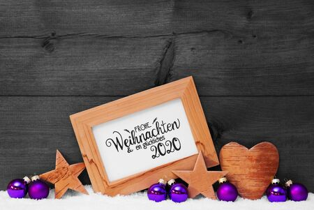 Frame With German Calligraphy Frohe Weihnachten Und Ein Glueckliches 2020 Mean Merry Christmas And A Happy 2020. Purple Christmas Decoration Like Ball, Star And Heart. Gray Wooden Background With Snow