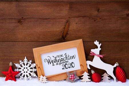 German Calligraphy Frohe Weihnachten Und Ein Glueckliches 2020 Mean Merry Christmas And Happy 2020. Red Christmas Ornament Like Tree, Ball And Wooden Deer. Wooden Background With Snow