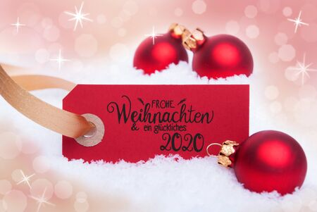 Red Label With German Calligraphy Frohe Weihnachten Und Ein Glueckliches 2020 Mean Merry Christmas And A Happy 2020. Christmas Ball Ornament. Shiny Bokeh Background With Snow