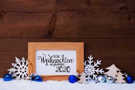 German Calligraphy Frohe Weihnachten Und Ein Glueckliches 2020 Mean Merry Christmas And Happy 2020. Blue Christmas Ornament Like Tree, Snowflake And Ball. Wooden Background With Snow