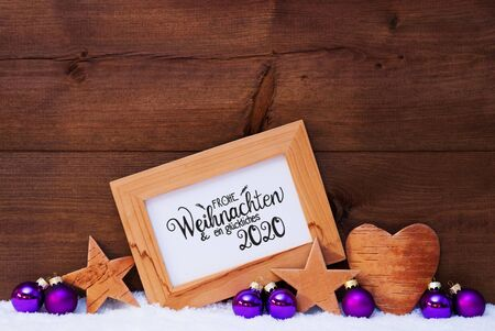 Frame With German Calligraphy Frohe Weihnachten Und Ein Glueckliches 2020 Mean Merry Christmas And A Happy 2020. Purple Christmas Decoration Like Ball, Star And Heart. Wooden Background With Snow Stock Photo