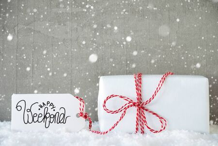 Label With Egnlish Calligraphy Happy Weekend. One White Gift With Red Bow. Gray Concrete Background With Snow And Snowflakes Stock fotó