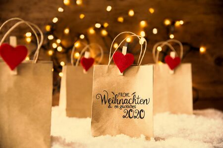 Christmas Shopping Bags On Snow With German Calligraphy Frohe Weihnachten Und Ein Glueckliches 2020 Mean Merry Christmas And Happy 2020. Bright Glowing Lights In Background Banco de Imagens