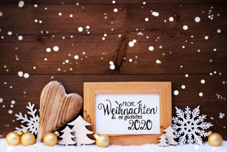 German Calligraphy Frohe Weihnachten Und Ein Glueckliches 2020 Mean Merry Christmas And Happy 2020. Golden Christmas Ornament Like Ball, Heart And Tree. Wooden Background With Snow And Snowflakes