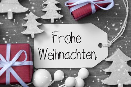 One Label With German Calligraphy Frohe Weihanchten Means Merry Christmas. Christmas Decoration Like Gifts And Trees. Wooden Background WIth Snowflakes Stock Photo