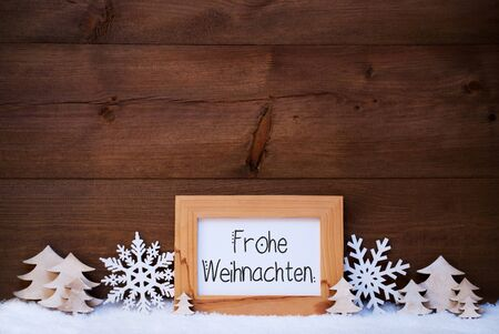 German Calligraphy Frohe Weihnachten Mean Merry Christmas. White Christmas Ornament Like Snowflake And Tree. Wooden Background With Snow