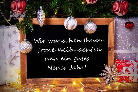 Blackboard With German Text Wir Wuenschen Frohe Weihnachten Und Ein Gutes Neues Jahr Means Merry Christmas And Happy New Year. Christmas Tree With Ball, Gifts And Fairy Lights Zdjęcie Seryjne
