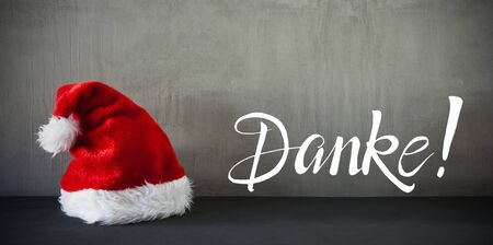 German Calligraphy Danke Means Thank You. Red Santa Claus Hat. Grungy Concrete Background