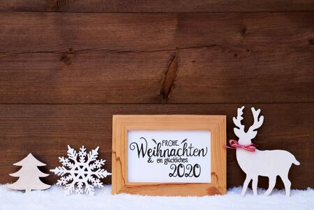 German Calligraphy Frohe Weihnachten Und Ein Glueckliches 2020 Mean Merry Christmas And Happy 2020. White Christmas Ornament Like Snowflake, Tree And Wooden Deer. Wooden Background With Snow Banco de Imagens