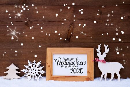 German Calligraphy Frohe Weihnachten Und Ein Glueckliches 2020 Mean Merry Christmas And Happy 2020. White Christmas Ornament Like Tree And Wooden Deer. Wooden Background With Snow And Snowflakes Banco de Imagens