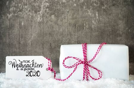 Label With German Calligraphy Frohe Weihnachten Und Ein Glueckliches 2020 Mean Merry Christmas And Happy 2020. White Christmas Present On Grungy Cement Background With Snow. Banco de Imagens