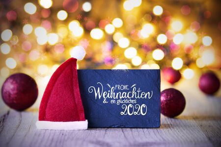 Sighn Wth German Calligraphy Frohe Weihnachten Und Ein Glueckliches 2020 Mean Merry Christmas And Happy 2020. Purple Christmas Ball Ornament With Red Santa Hat. Sparkling Lights Background