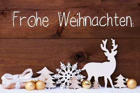 German Calligraphy Frohe Weihnachten Means Merry Christmas. Golden Christmas Decoration Like Tree, Gift, Ball And Reindeer. Wooden Background With Snow