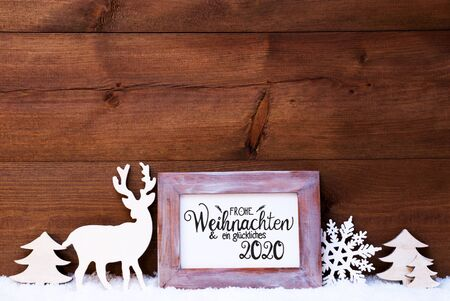Vintage Frame With German Calligraphy Frohe Weihnachten Und Ein Glueckliches 2020 Means Merry Christmas And A Happy 2020. Christmas Decoration Like Deer And Tree. Wooden Background With Snow