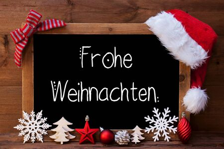 Chalkboard With German Calligraphy Frohe Weihnachten Mean Merry Christmas. Christmas Decoration Like Tree, Ball, Snowflake And Santa Hat. Wooden Background
