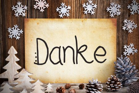 Old Paper With German Text Danke Means Thank You. Christmas Decoration Like Tree, Fir Cone And Snowflakes. Brown Wooden Background