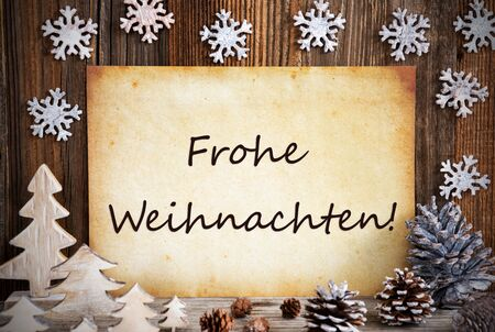Old Paper With German Text Frohe Weihnachten Means Merry Christmas. Christmas Decoration Like Tree, Fir Cone And Snowflakes. Brown Wooden Background