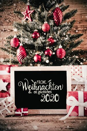 German Calligraphy Frohe Weihnachten Und Ein Glueckliches 2020 Means Merry Christmas And A Happy 2020. Christmas Tree With Gifts, Red Ball Ornament And Sowflakes