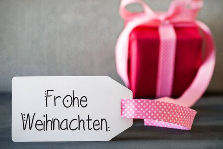 German Calligraphy Frohe Weihnachten Means Merry Christmas. Pink Present With Bow And Label. Gray Concrete Background 版權商用圖片