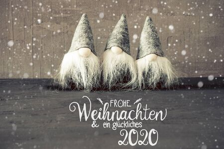 German Calligraphy Frohe Weihnachten Und Ein Glueckliches 2020 Means Merry Christmas And A Happy 2020. Thress Santa Claus With Hat And Concrete Background.