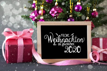 Blackboard With German Calligraphy Frohe Weihnachten Und Ein Glueckliches 2020 Means Merry Christmas And Happy 2020. Christmas Tree With Purple Ball Ornament, Pink Gift And Bokeh Effect And Snowflakes 版權商用圖片