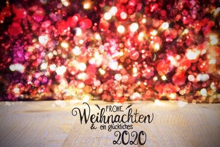 German Calligraphy Frohe Weihnachten Und Ein Glueckliches 2020 Means Merry Christmas And Happy 2020. Red Christmas Background With Sparkling Lights And Wood