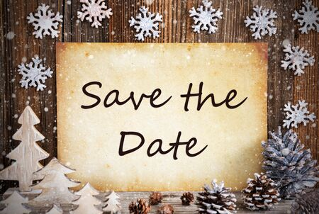 Old Paper With English Text Save The Date. Christmas Decoration Like Tree, Fir Cone And Snow. Brown Wooden Background Фото со стока