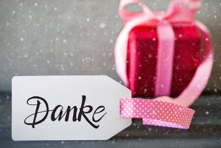 German Calligraphy Danke Means Thank You. Pink Present With Bow And Label. Gray Concrete Background And Snowflakes 版權商用圖片