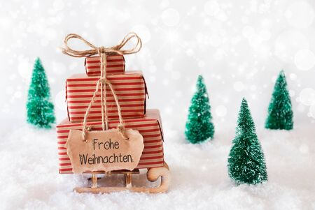 Sled With Christmas Gift And Label With GermanFrohe Weihnachten Means Merry Christmas. Snow With Christmas Tree And Gray Sparkling Background