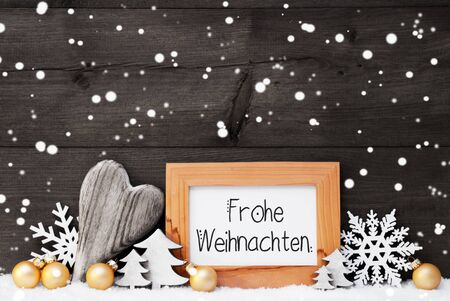 German Calligraphy Frohe Weihnachten Mean Merry Christmas. Golden Christmas Ornament Like Ball, Heart And Tree. Gray Wooden Background With Snow And Snowflakes Stock Photo