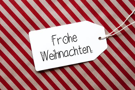 Label With German Calligraphy Frohe Weihnachten Mean Merry Christmas. Red Wrapping Paper As Background