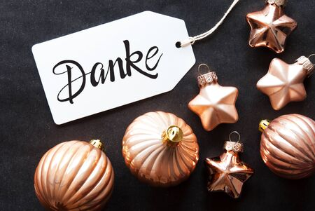 One Label With German Calligraphy Danke Means Thank You. Golden Christmas Ball Ornament On Black Background. 版權商用圖片
