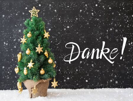 German Calligraphy Danke Means Thank You. Christmas Tree With Golden Ball Ornament And Snow And Snowflakes. Black Wooden Background