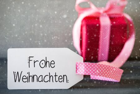 German Calligraphy Frohe Weihnachten Means Merry Christmas. Pink Present With Bow And Label. Gray Concrete Background And Snowflakes 版權商用圖片