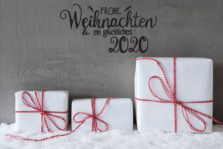 Label With German Calligraphy Frohe Weihnachten Und Ein Glueckliches 2020 Means Merry Christmas And A Happy 2020. Three White Gifts With Red Bow. Gray Concrete Background With Snow